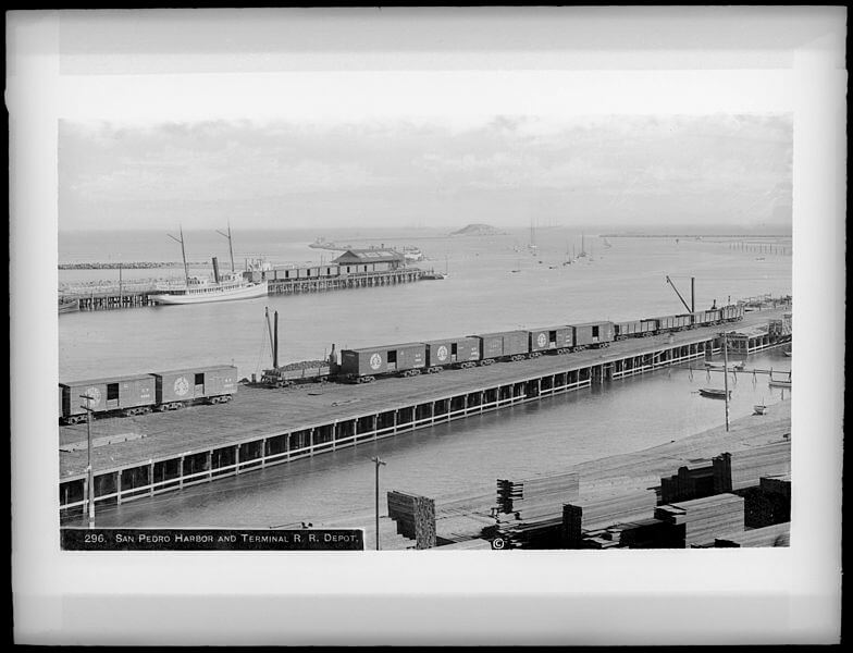 Port of Los Angeles, San Pedro Harbor and Terminal Railroad Depot, around 1905. The view is from the dock southwest to the mouth of the breakwater. Deadman's Island has not yet been removed, it is visible on the left side of the mouth. The ships which appear include both steam and sailing vessels. A railroad runs in the foreground, to the docks on which lumber has been unloaded. Another railroad appears in the background, on the other side of the channel. As Los Angeles tripled its population between 1900 and 1910, causing the real estate and construction industries to boom, large quantities of lumber were imported from the Pacific Northwest.