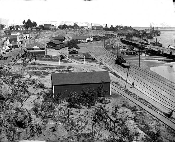 "View of San Pedro, timber wharves, engine number ""1614"" on Southern Pacific Railroad tracks, and buildings at San Pedro harbor (Port of Los Angeles), Los Angeles, California. Brick commercial buildings are on Front Street (Harbor Boulevard) near the Southern Pacific Passenger Station. Frame houses and a horse-drawn wagon are on Nob Hill. A man is beside railroad tracks near a sign that reads: ""Use Mermaid Queen Soap, Best Made."" Schooners are in San Pedro Bay. [between 1891 and 1910?]"