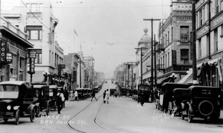 (1920) - Scenic view of 6th Street in San Pedro. This street is a busy area with many retail stores on both sides of the street. There are two banks, two pool halls, a cafe, shoe store, drug store, a dentist, and even rooms for rent. Automobiles can be seen parked up and down the street. (photo courtesy Water and Power Associates)